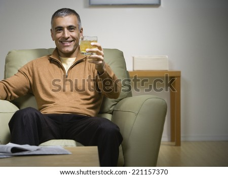 Middle Eastern man holding up drink - stock photo