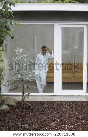 Middle Eastern man looking out glass wall - stock photo