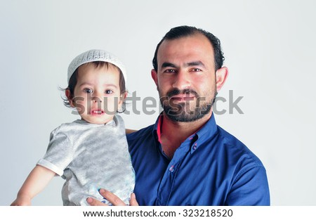 Middle Eastern Muslim dad holding his son against a grey background - stock photo
