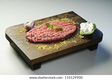 Middle eastern raw kibbe arranged on wooden board. - stock photo