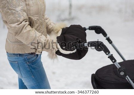 Middle eastern woman with coupling for stroller going for a walk in a park during lovely winter afternoon - stock photo