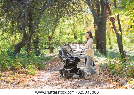 Middle eastern woman with stroller going for a walk in a park during lovely autumn afternoon