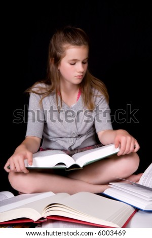Middle school girl sitting on the floor surrounded by thick books and reading from one.
