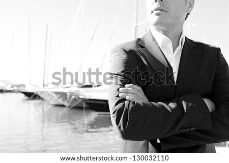 Middle section of a smart businessman wearing a suit and standing by a luxury yachts marine with his arms crossed. Black and white image. - stock photo