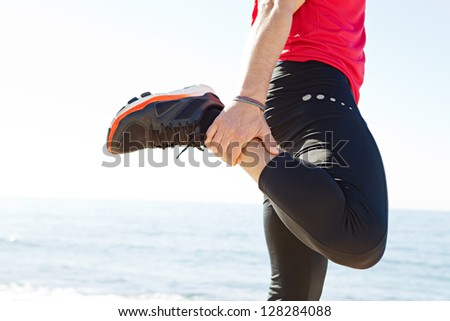 Middle section of a sports man body stretching his leg back while standing by the sea on a sunny day, against a blue sky. - stock photo