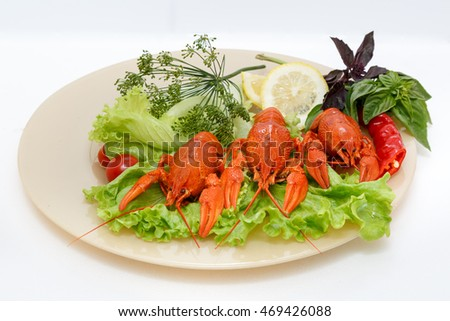 Middle sized boiled crawfish beautifully laid out over plate with salad, lemon, basil leaf, red paper, dill and cherry tomatoes on a white background