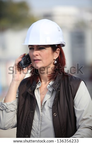middleaged female architect making a call in construction site