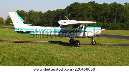 MIDDLESEX, VA - SEPTEMBER 27, 2014: A small green and white personal airplane/aircraft on the runway in the wings wheels and keels annual show at the Hummel airfield airstrip in Middlesex VA