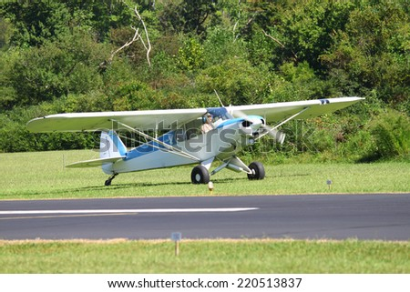 MIDDLESEX, VA - SEPTEMBER 27, 2014: A Super Cub on the side of the runway at Hummel field airport in the wings wheels and keels annual show at the Hummel airfield airstrip in Middlesex VA