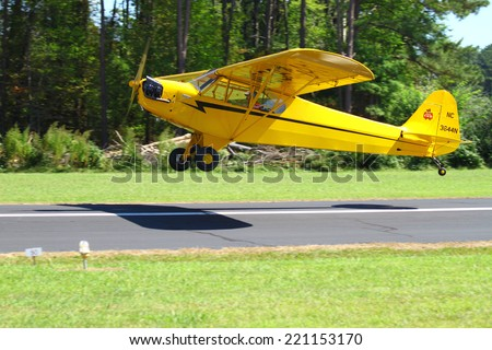 MIDDLESEX, VA - SEPTEMBER 27, 2014: A yellow piper cub as it lands at the Hummel field airport in the wings wheels and keels annual show at the Hummel airfield airstrip in Middlesex VA
