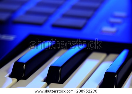 MIDI Controller Keyboard in Blue Light - stock photo
