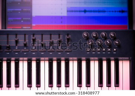 Midi keyboard and controller with faders and buttons. Waveforms in a DAW are visible in the background