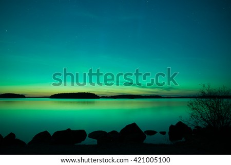 Midnight light with northern lights over calm lake (Aurora borealis) - stock photo
