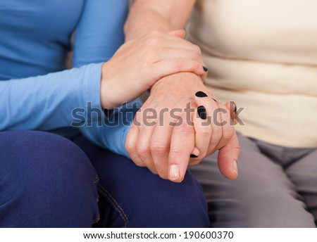 Midsection closeup of female caregiver consoling senior woman