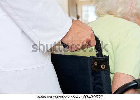 Midsection of a doctor assisting senior patient sitting in a wheel chair - stock photo