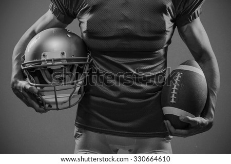 Midsection of American football player in red jersey holding helmet and ball against grey background - stock photo