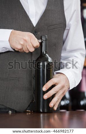 Midsection Of Bartender Opening Wine Bottle
