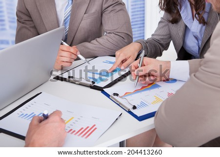 Midsection of business people discussing over graph at table in office - stock photo