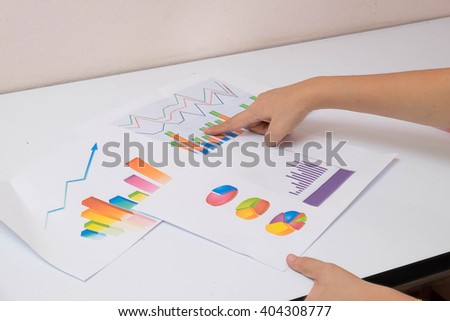 Midsection of business people discussing over graph at table in office