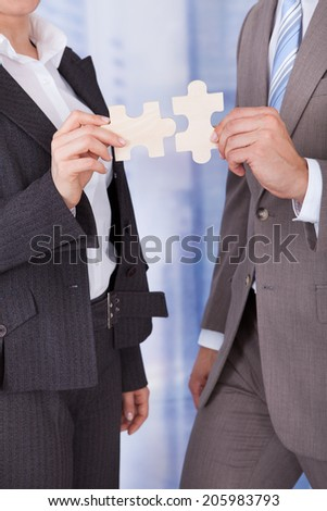 Midsection of businessman and businesswoman joining jigsaw pieces in office