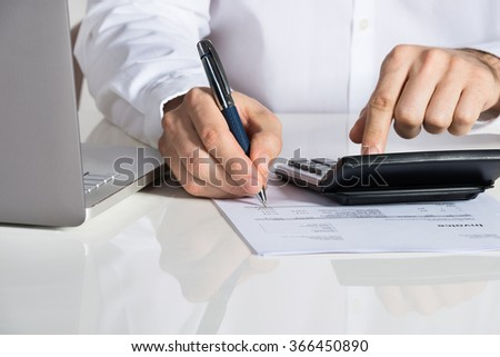 Midsection of businessman calculating invoice by laptop at office desk - stock photo