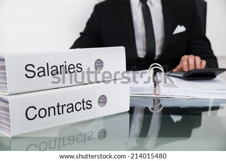 Midsection of businessman calculating salaries and contracts at desk in office