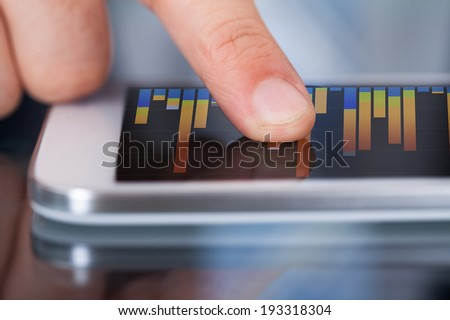 Midsection of businessman comparing graphs on digital tablet at desk in office - stock photo
