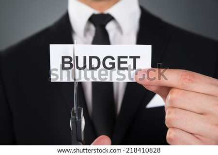 Midsection of businessman cutting the word Budget on paper with scissors over gray background - stock photo