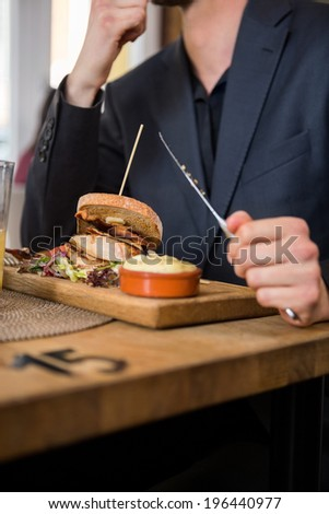 Midsection of businessman eating food in restaurant