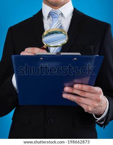 Midsection of businessman examining document on clipboard with magnifying glass against blue background