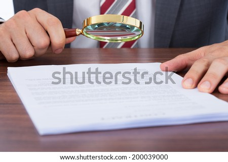 Midsection of businessman examining document with magnifying glass at desk - stock photo