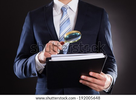Midsection of businessman examining documents with magnifying glass against black background - stock photo