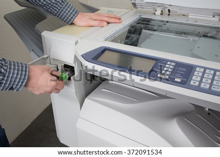Midsection of businessman fixing cartridge in photocopy machine at office