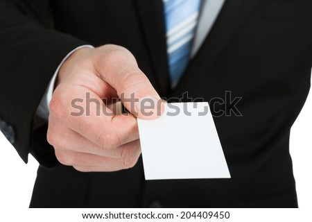 Midsection of businessman holding blank visiting card over white background - stock photo