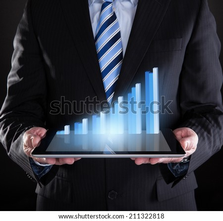 Midsection of businessman holding digital tablet with graph representing growth - stock photo