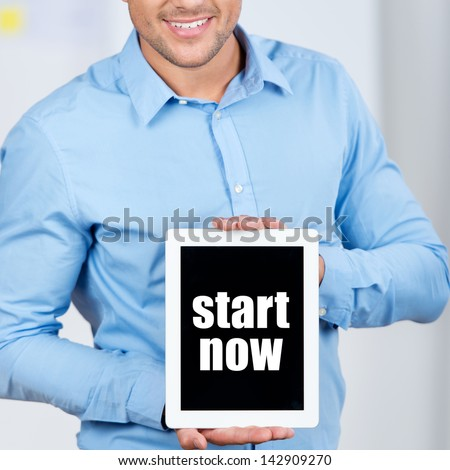 Midsection of businessman holding digital tablet with Start Now sign in office - stock photo