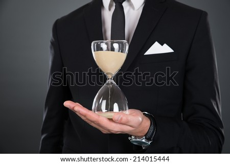 Midsection of businessman holding hourglass isolated against gray background - stock photo