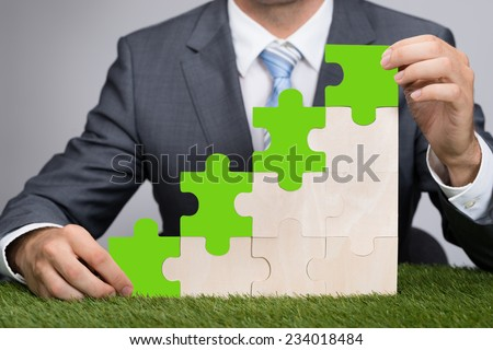 Midsection of businessman holding jigsaw graph on grass representing go green concept - stock photo