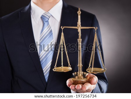 Midsection of businessman holding justice scale against black background - stock photo