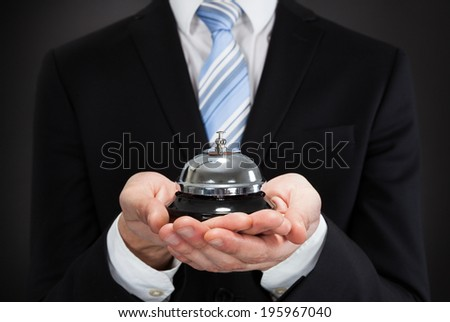 Midsection of businessman holding service bell against black background - stock photo