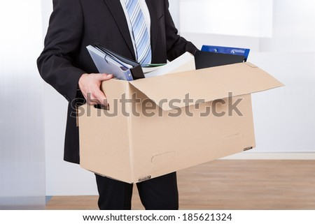 Midsection of businessman moving out with cardboard box from office - stock photo