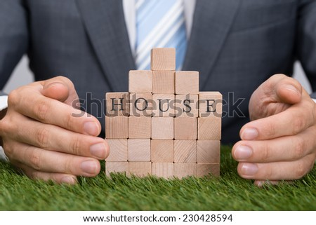Midsection of businessman protecting house blocks on grass - stock photo
