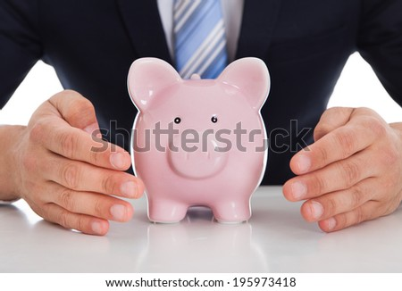 Midsection of businessman protecting piggybank with cupped hands on desk against white background