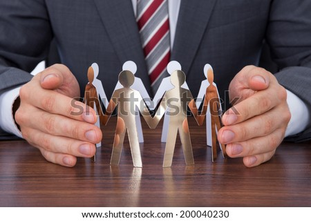 Midsection of businessman protecting team of paper people on desk - stock photo