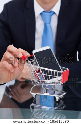 Midsection of businessman pushing smartphone in shopping cart at desk - stock photo