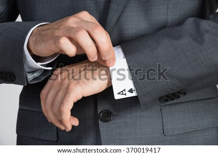 Midsection of businessman removing ace cards from sleeve in office