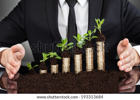 Midsection of businessman's hands protecting coins in saplings representing responsible business - stock photo