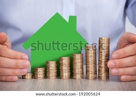 Midsection of businessman's hands protecting stacked euro coins and house model in office - stock photo