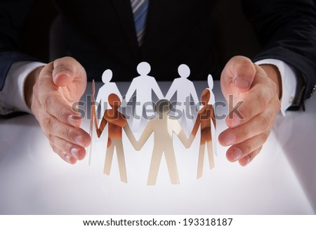Midsection of businessman's hands protecting team of paper people on desk