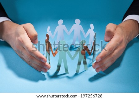 Midsection of businessman's hands protecting team of paper people on desk - stock photo